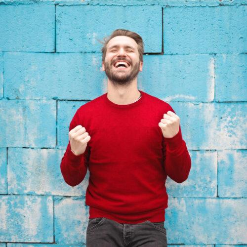 happy-guy-outside-in-red-sweater